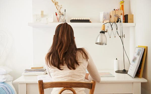 Rear view shot of a young woman studying at her desk at home